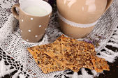 Pitcher and cup of milk with cookies on wooden table close-up — Stock Photo