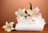 Stack of towels with pink lily on a brown background — Stock Photo