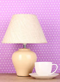 Table lamp and cup on purple polka dot background — Stock Photo