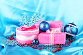 Beautiful pink gifts with blue Christmas balls, snowflakes and beads on blue background — Stock Photo