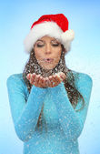 Beautiful young woman blowing snow, on blue background — Stock Photo