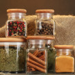 Jars with spices on wooden table on brown background — Stock Photo