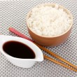Bowl of rice and chopsticks on grey mat — Stock Photo
