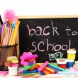 The words 'Back to School' written in chalk on the small school desk with various school supplies close-up isolated on white — Stockfoto