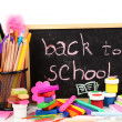 The words 'Back to School' written in chalk on the small school desk with various school supplies close-up isolated on white — Foto Stock