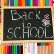 The words 'Back to School' written in chalk on the small school desk with various school supplies close-up - Stock Photo