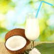 Glass of coconut milk and coconuts on green background close-up — Stock Photo #14342717
