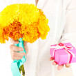 Woman holds a box with a gift and flowers on white background close-up — Stock Photo