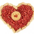 Stock Photo: Delicious peanut butter in glass plate on picture of peanuts in form of heart isolated on white close-up