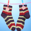 Pair of knit striped socks hanging to dry over blue background — Stock Photo #14345269