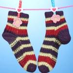 par de tricotar meias listradas pendurado para secar sobre fundo azul — Foto Stock #14345269