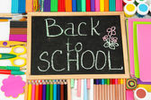 The words 'Back to School' written in chalk on the small school desk with various school supplies close-up — Stockfoto