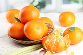 Tangerines with leaves in a beautiful basket, on white wooden table — Stock Photo