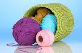 красочные пряжа для вязания в зеленой корзине на синем фоне — Стоковое фото