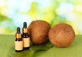 Kokosolja i flaskor med kokosnötter på grön bakgrund — Stockfoto
