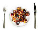 Castañas asadas en el plato blanco con tenedor y cuchillo aislado en blanco — Foto de Stock