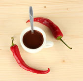 White cup with hot chocolate and chili pepper on wooden background — Stock Photo