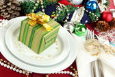 Small Christmas gift on plate on serving Christmas table background close-up — Stock Photo