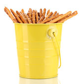 Tasty crispy sticks in yellow pail isolated on white — Stock Photo