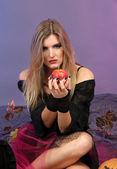 Halloween heks met rode appel op kleur achtergrond — Stockfoto