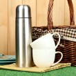 Stock Photo: Metal thermos with cups, plates and basket on grass on wooden background