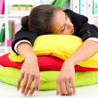 Tired business woman with pillows sitting at the table and sleeps — Stock Photo