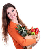 Woman holding a grocery bag full of fresh vegetables and fruits isolated on white — Stock Photo
