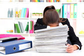 Tired business woman with documents in her workplace — Stock Photo