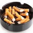 Cigarette butts in ashtray isolateed on white - Stock Photo
