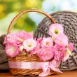 Bouquet of eustoma flowers in basket, on wooden table, on green background — Stock Photo