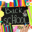 The words 'Back to School' written in chalk on the small school desk with various school supplies close-up — Stock Photo #14500683