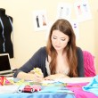 图库照片: Beautiful young dressmaker in workroom