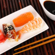 Delicious sushi served on plate on bamboo mat - Stock Photo