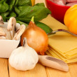 Vegetarian lasagna ingredients on wooden background - Stock Photo
