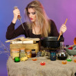 Halloween witch stirring in poison soup in her cauldron on color background - Stock Photo