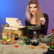 Halloween witch preparing poison soup in her cauldron on color background — Stock Photo #14501227