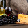 Bottles and glasses of wine, cheese and grapes on grey background — Stock Photo #14501287