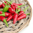 Little hot peppers on wicker mat isolated on white - Stock Photo