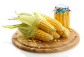 Fresh corn and preserve corn on wooden cutting board, isolated on white — Stock Photo