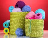 красочные пряжа для вязания в зеленой корзине на красном фоне — Стоковое фото