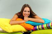 красивая молодая девушка с подушками на сером фоне — Стоковое фото