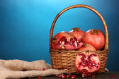 Ripe pomegranates on basket on wooden table on blue background — Stock Photo