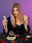 Renkli arka plan üzerinde voodoo bebek ile cadı — Stok fotoğraf