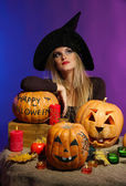 Halloween witch with pumpkins on color background — Stock Photo
