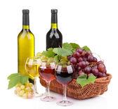 Flaskor och glas vin och druvor i korg, isolerad på vit — Stockfoto