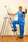 Handyman drill standing on ladder — Stockfoto