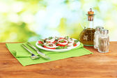 Salad with capers in the plate on bright green background — Stock Photo