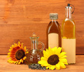 Oil in bottles, sunflowers and seeds, on wooden background — Stock Photo