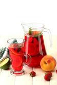 Sangria in glas und glas mit früchten, auf weißer holztisch, isoliert auf weiss — Stockfoto