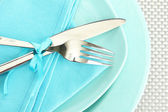 Blue empty plates with fork and knife on a grey tablecloth — Stock Photo